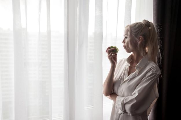 La ragazza in camicia bianca dell'uomo beve caffè alla finestra.