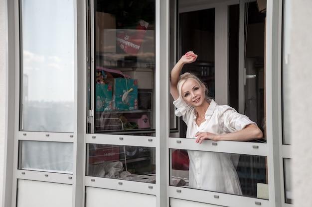 La ragazza in camicia da uomo bianca guarda fuori dalla finestra ed è emotiva. ritratto di bella donna. comfort domestico e attesa. femmina slava al mattino. emozioni e relax. concetto di esperienze in famiglia
