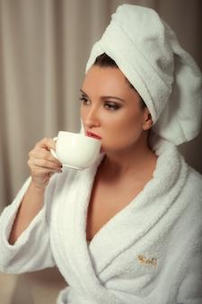 Una ragazza in una veste bianca dopo una doccia beve caffè dalla sua tazza in camera da letto