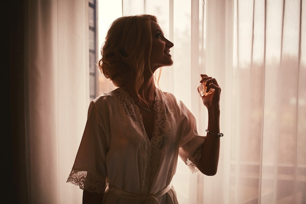 Una ragazza in una vestaglia di raso bianco con una scollatura e una manicure francese tiene una bottiglia di profumo