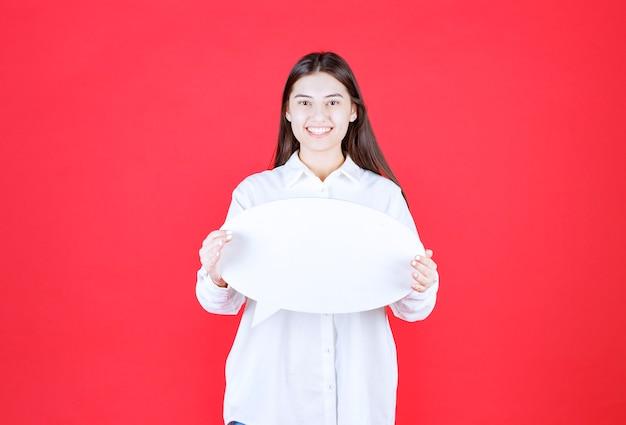 Ragazza in camicia bianca che tiene in mano una bacheca informativa ovale e si sente positiva