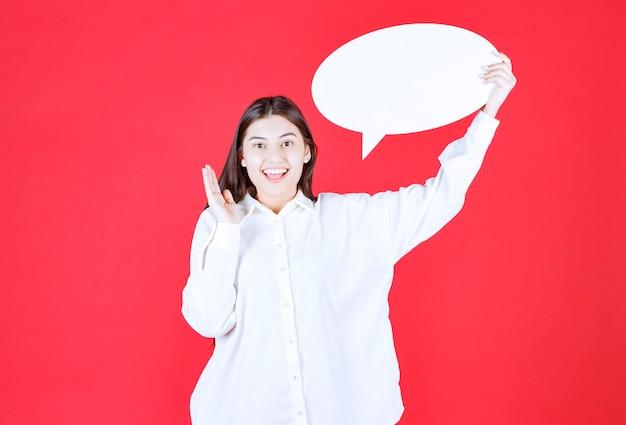 Ragazza in camicia bianca che tiene in mano un pannello informativo ovale e grida e chiama qualcuno