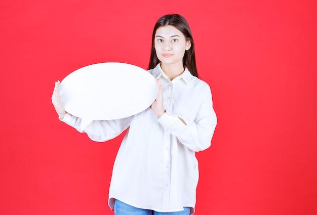 Ragazza in camicia bianca con in mano un pannello informativo ovale