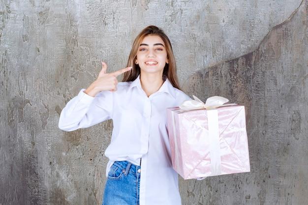 Ragazza in camicia bianca che tiene una confezione regalo rosa avvolta con un nastro bianco.