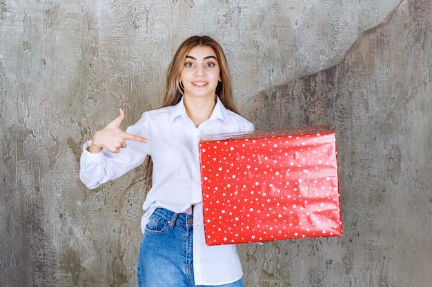 Ragazza in camicia bianca con in mano una confezione regalo rossa con puntini bianchi sopra