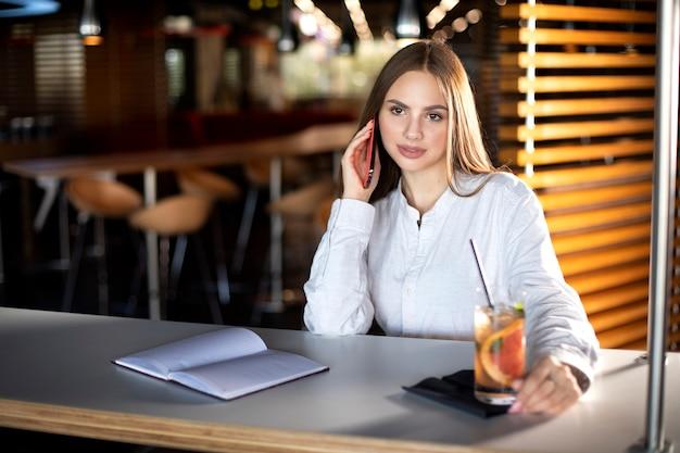 La ragazza in una camicia bianca si siede a un tavolo e parla al telefono, accanto a un tavolo c'è un drink e un taccuino