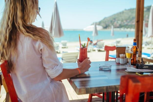 La ragazza in una camicia bianca si siede con un cocktail in un ristorante vicino al mare