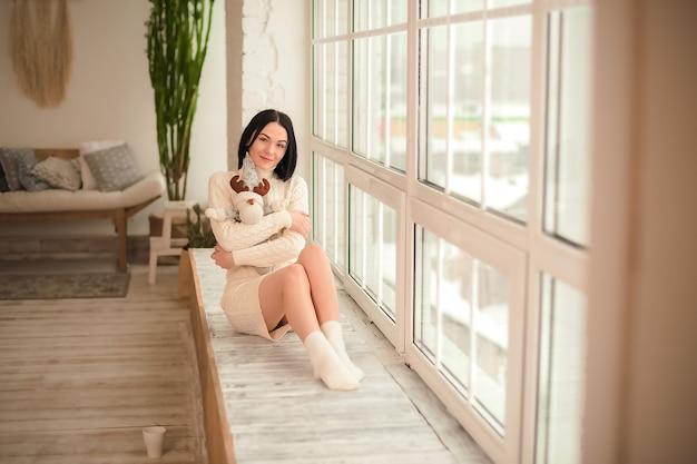 Ragazza in un vestito maglione bianco contro una grande finestra