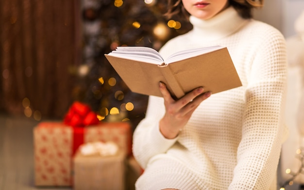 Una ragazza in un maglione bianco si siede e legge un libro sullo sfondo di un albero di natale e regali