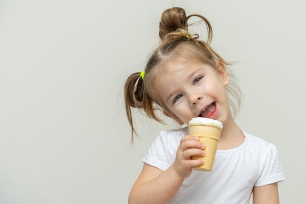 Ragazza in una maglietta bianca che mangia il gelato e sorridente. bambini e dolci
