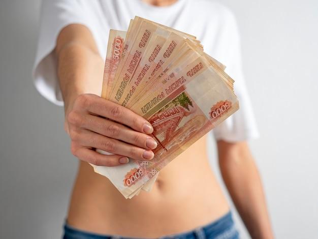 Una ragazza con una maglietta bianca a pancia scoperta tiene nella mano tesa un fascio di banconote da 5000 rubli russi.