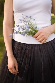Ragazza con una maglietta bianca e una gonna nera soffice con in mano un bellissimo mazzo di fiori non ti scordar di me