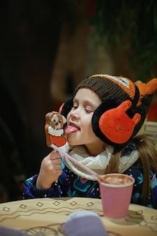 Una ragazza in abiti invernali si siede in un caffè lecca un pan di zenzero e beve cioccolata calda