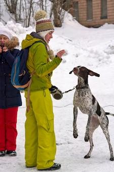 Una ragazza in abiti sportivi invernali gioca con un cane
