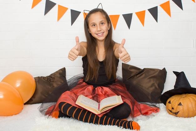 Ragazza in costume da strega con un libro di stregoneria che celebra halloween a casa mostra le sue dita cool