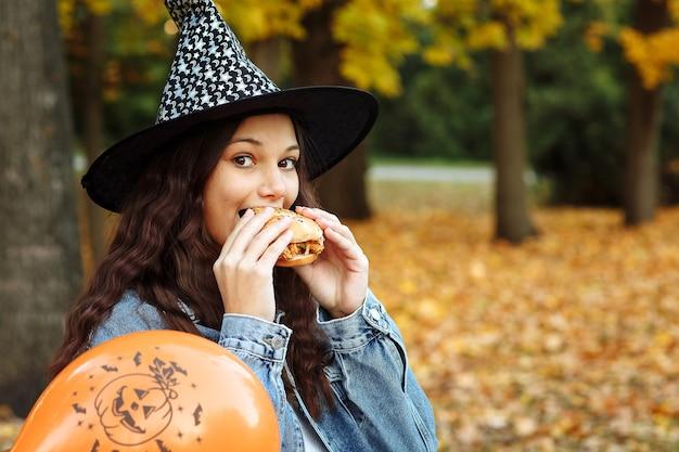 Una ragazza con un cappello da strega accanto a un palloncino arancione per halloween mangia un hamburger in un parco autunnale