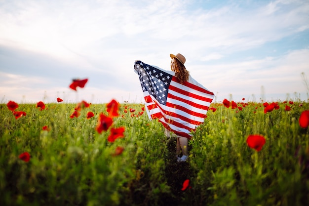 Ragazza con bandiera americana in posa in un campo di papaveri