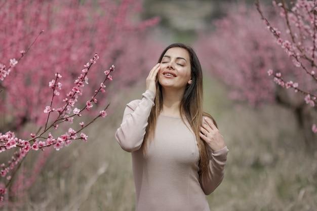 Ragazza con la figura attraente nella primavera dei vestiti stretti nel giardino
