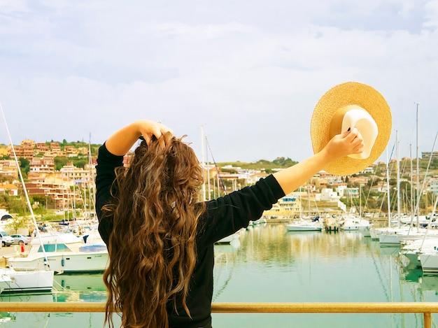 Ragazza con capelli lunghi impressionanti e cappello in mano sul porto di mare con gli yacht.