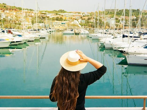 Ragazza con i capelli lunghi e cappello impressionante sul porto di mare con gli yacht.