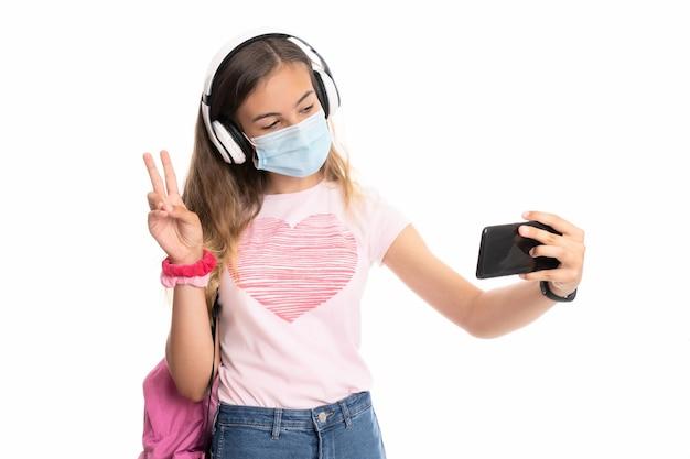 Ragazza con zaino, cuffie e maschera prendendo un selfie