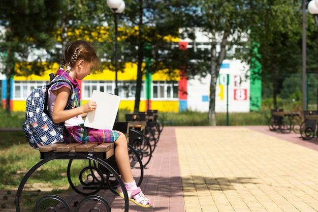 Ragazza con uno zaino seduto su una panchina e leggendo un libro vicino alla scuola. ritorno a scuola, orario delle lezioni, diario con i voti. istruzione, classi della scuola primaria, 1 settembre