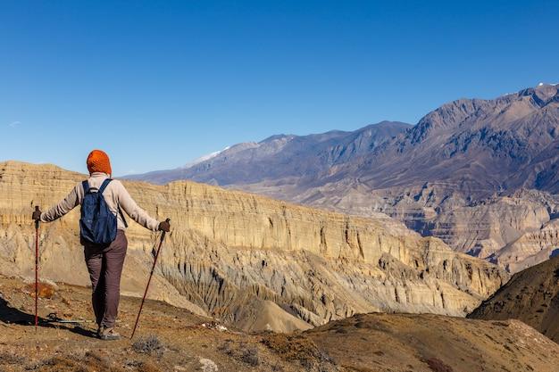 Ragazza con uno zaino e bastoncini da trekking guarda le montagne, il nepal. la ragazza turistica sta indietro.