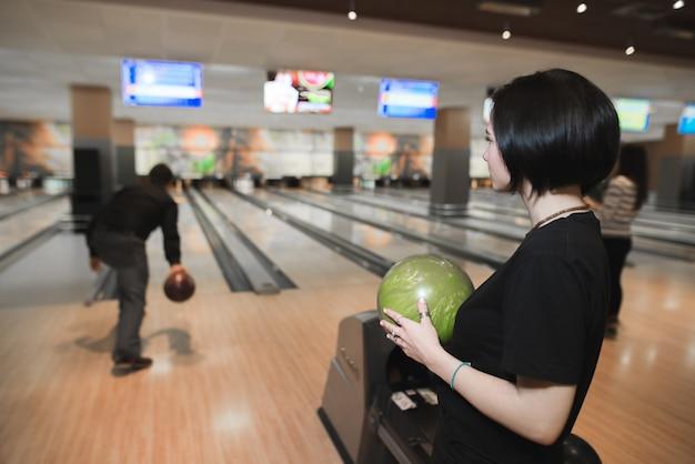 Ragazza con una palla da bowling tra le mani guarda il gioco di un'altra persona. gioco di bowling.