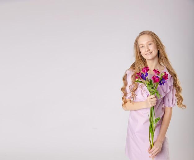 Ragazza con bellissimi fiori in abiti viola