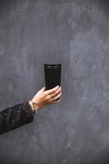 Ragazza con la bella mano manicure che tiene un bicchiere vuoto nero su un muro grigio