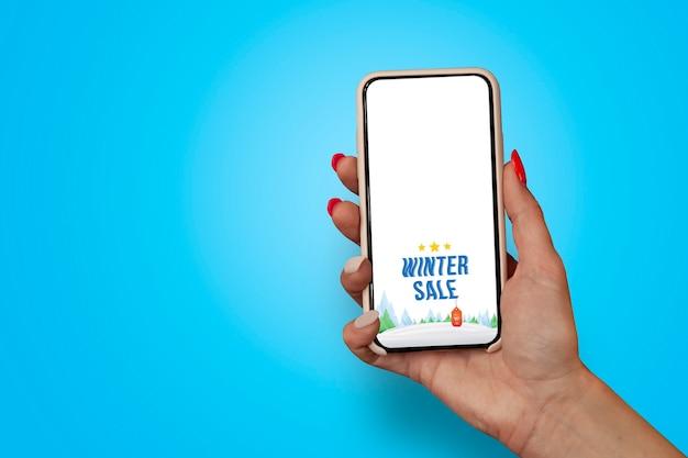 La ragazza con le belle unghie tiene il primo piano dello smartphone con la vendita di inverno dell'insegna.
