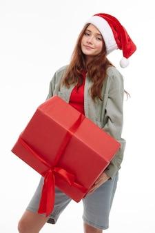 Ragazza con un grande regalo rosso nelle sue mani cappello di natale