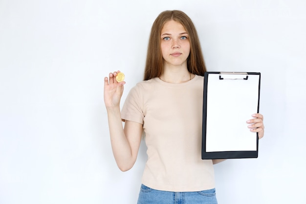 Ragazza con bitcoin e tablet su sfondo grigio. finanza e criptovalute