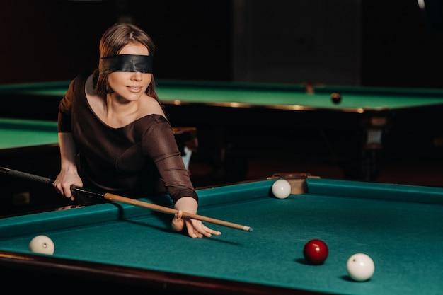Una ragazza con una benda e una stecca in mano in un club di biliardo. biliardo russo.