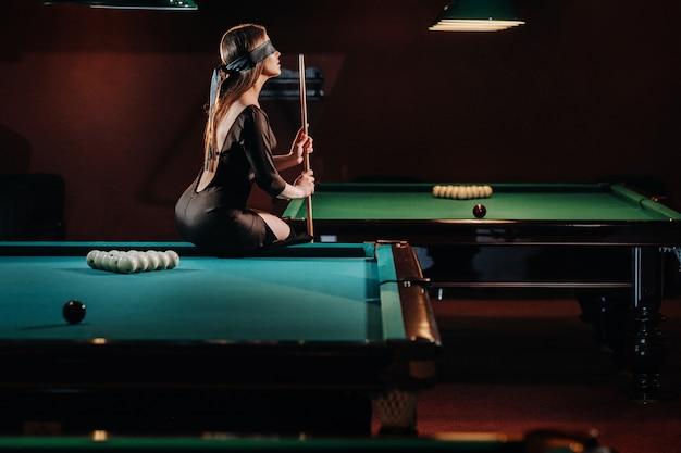 Una ragazza con una benda e una stecca in mano è seduta su un tavolo in un club di biliardo. biliardo russo.