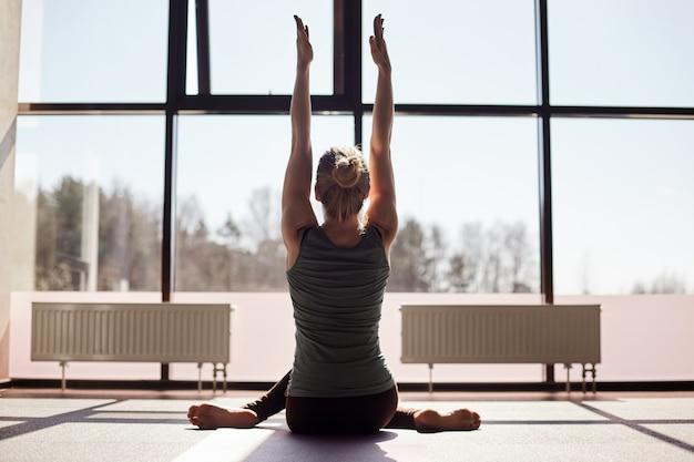 Una ragazza con i capelli biondi è seduta a gambe incrociate con le mani in aria, facendo yoga su una stuoia. la ragazza sta facendo yoga in un moderno studio con finestre panoramiche