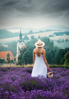 La ragazza con i capelli biondi cammina attraverso un campo di lavanda in montagna