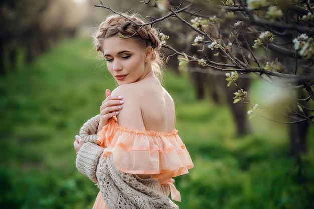 Ragazza con capelli biondi in un vestito leggero nel giardino fiorito. concetto di moda primavera femminile. ragazza in un bel vestito e maglione lavorato a maglia gode del tramonto in un giardino fiorito di pere