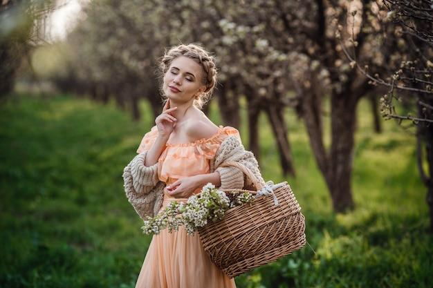 Ragazza con capelli biondi in un vestito leggero nel giardino fiorito. ragazza in un bel vestito e maglione lavorato a maglia si gode il tramonto in un giardino fiorito di pere, con un cesto di fiori