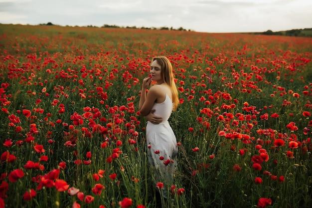 Ragazza con capelli biondi e abito bianco, in piedi in un campo di papaveri rossi