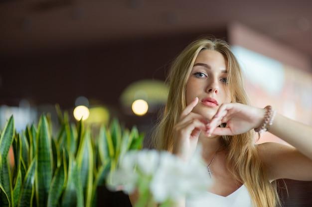 Ragazza con gli occhi azzurri che si siede sul caffè urbano. donna con acconciatura ondulata marrone. concetto di stile di vita.