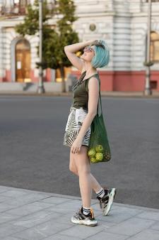 La ragazza con i capelli blu e la borsa stringhe cammina la sera in città