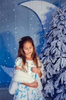Una ragazza con i capelli castani su uno sfondo blu e un albero coperto di neve, in abito carino
