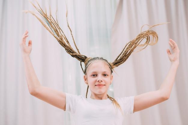 La ragazza con i capelli castani e le trecce con le trecce kanekalon