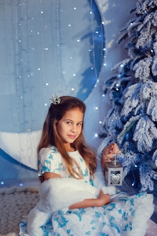 Una ragazza con i capelli castani accanto all'albero di natale