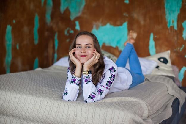 La ragazza con i capelli castani giace sul letto Foto Premium