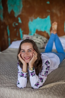 La ragazza con i capelli castani giace sul letto