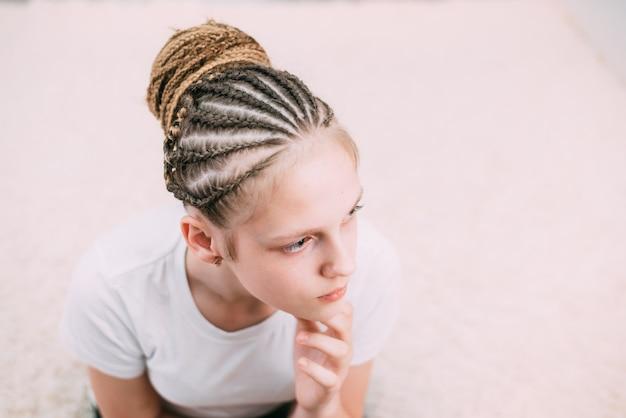Ragazza con capelli castani e trecce intrecciate con capelli artificiali