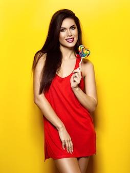 Ragazza con la maglietta rossa della caramella ragazza con la maglietta rossa della caramella sopra fondo giallo sopra fondo giallo. foto di alta qualità