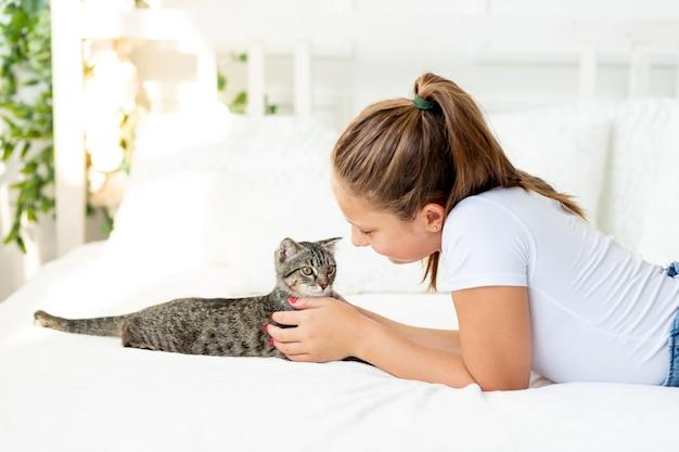 Ragazza con un gatto è sdraiato sul letto